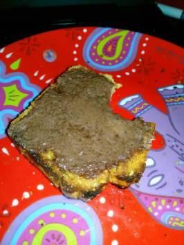 une tranche de pain cétogène toasté tartiné de beurre au cacao